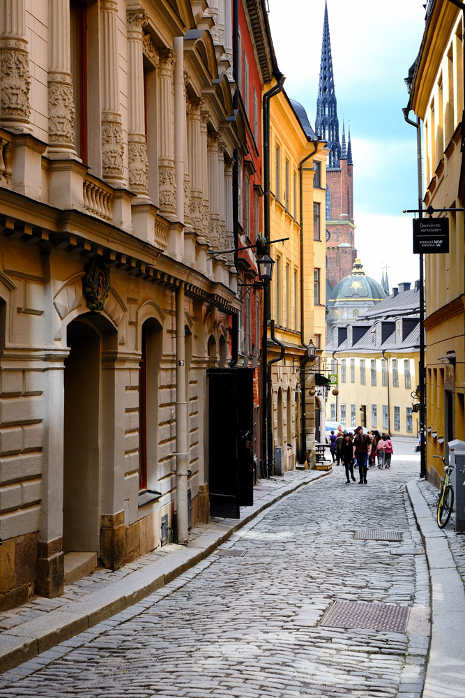 people walkinf alonf narrow street with church steeple in distance