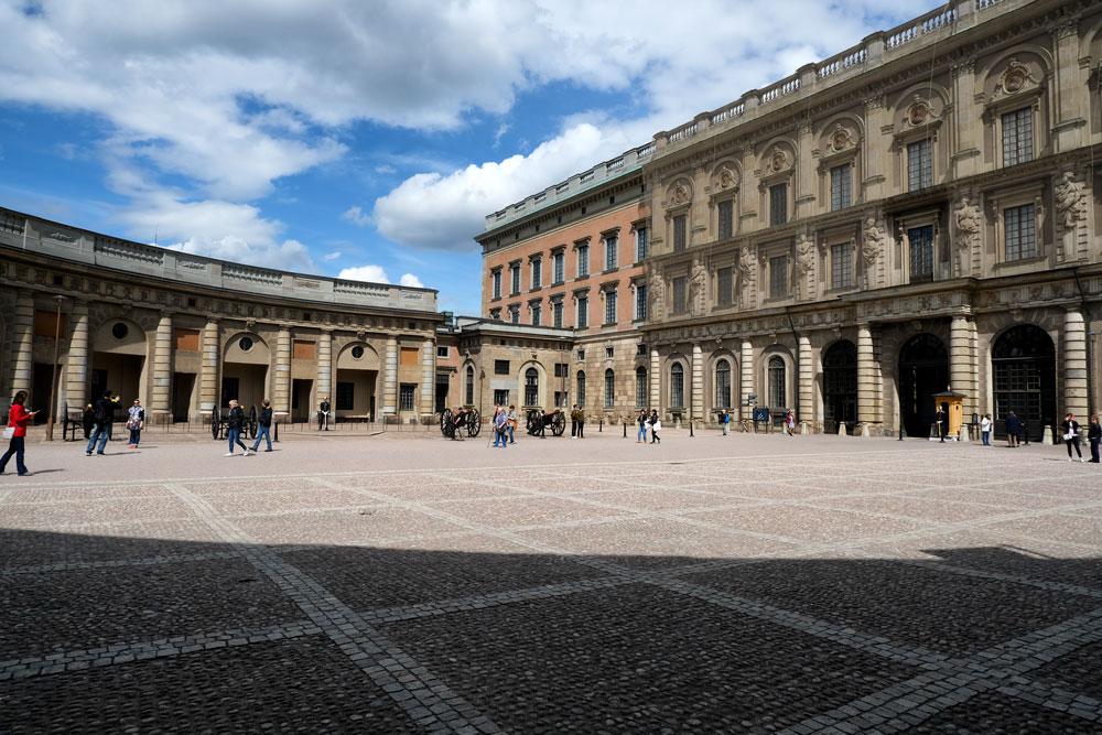 people walking across larke courtyard bordered by swedish royal palace buildings