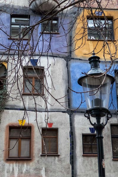 blue and grey and ochre higgledy piggeldy building with lampost