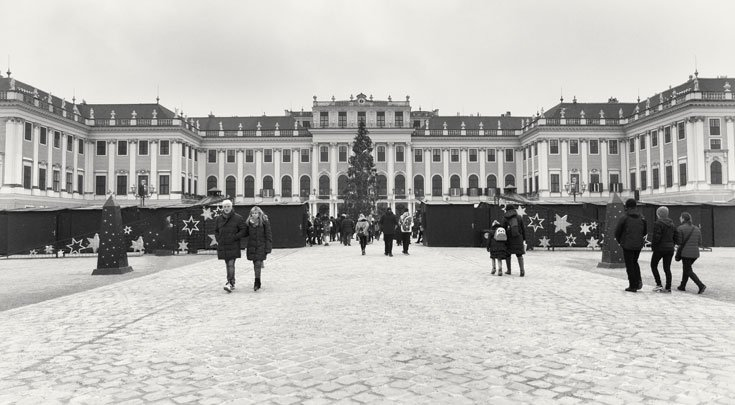 people walking in courtyard in front of palace building in vienna