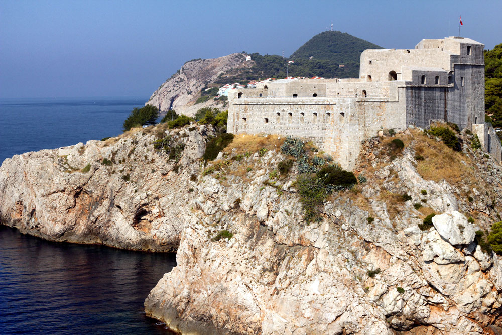 white fortress on cliff overlooking sea in dubrovnik
