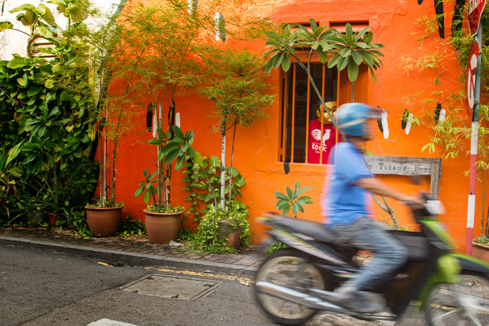 man on scooter going past an orange coloured house