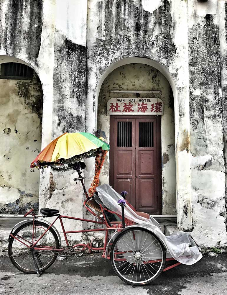 cycle rickshaw outside weathered chinese building in penang malaysia
