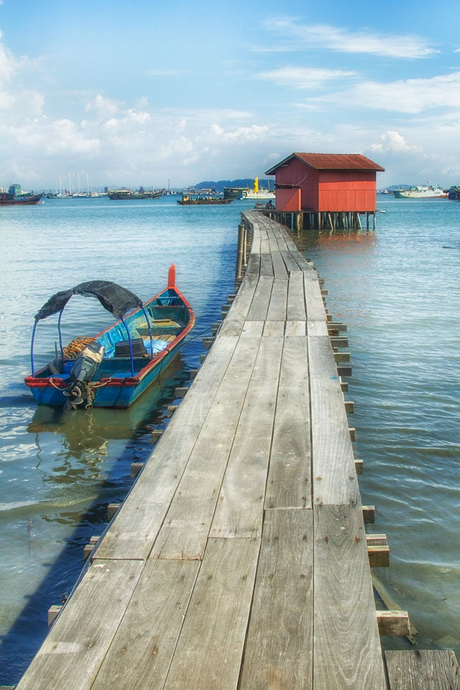 jetty reaching out to red wooden hut