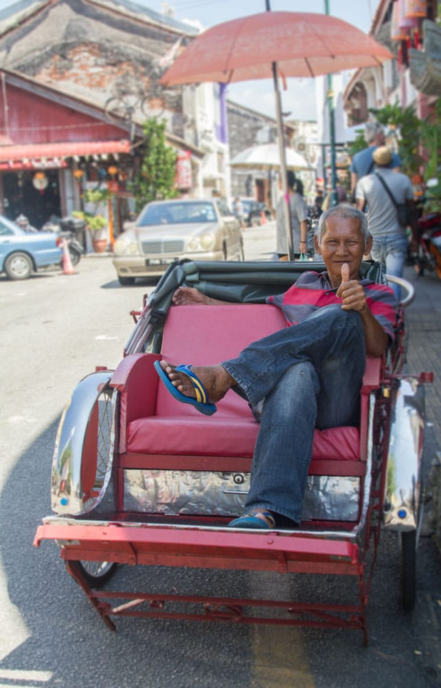man sitting in rickshaw giving a thumbs up sign