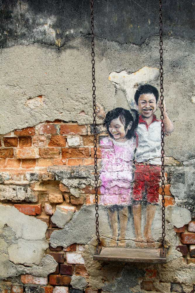 street art of girl and boy on swing in penang malaysia