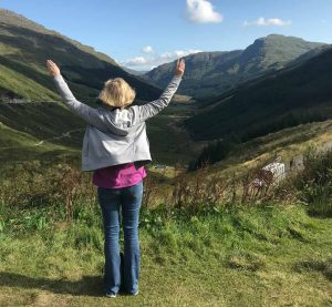 a woman who is a solo traveller in her 50s standing with arms outstretched in a scottish valley