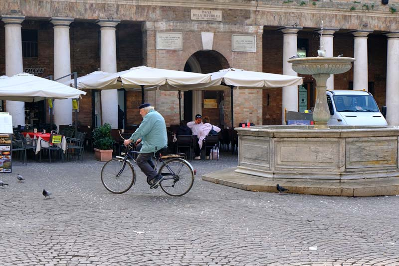 man-cycling-in-renaissance-piazza-with fountain n-urbino-italy