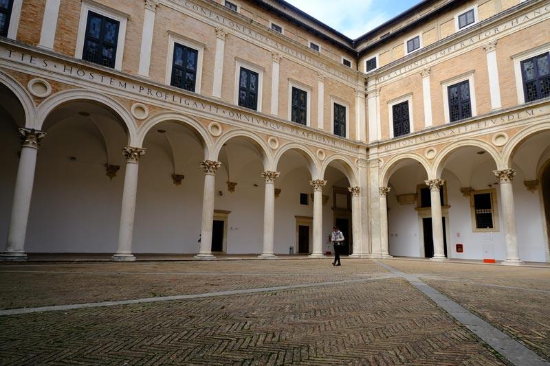 man walking across colonnaded renaissance-courtyard-of-palazzo-ducale-urbino
