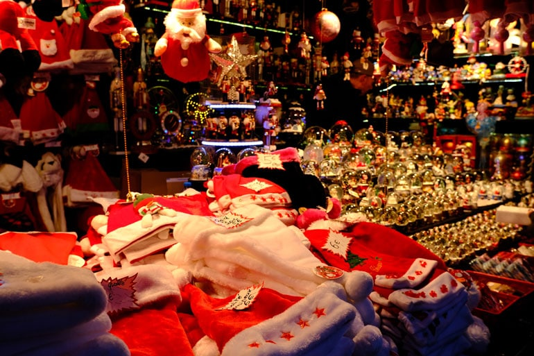 stall in a xmas market with decorations and santa hats