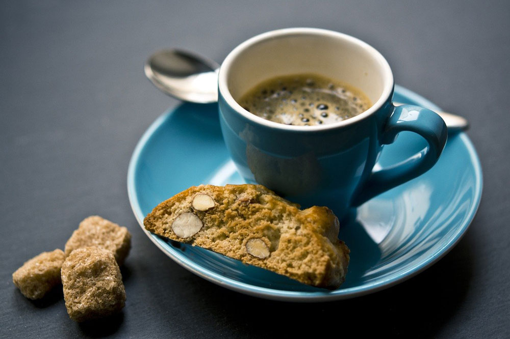 coffee in a blue espresso cup and suacer with spoon and biscuit