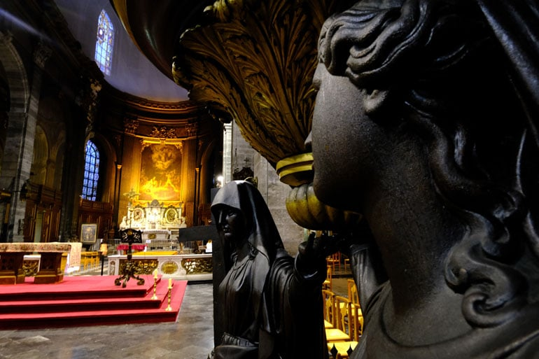 statue of angel in front of a church altar