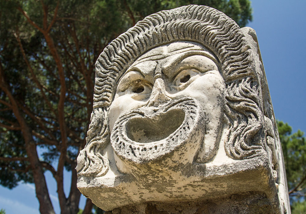 grimacing carved stone head at ostia antica