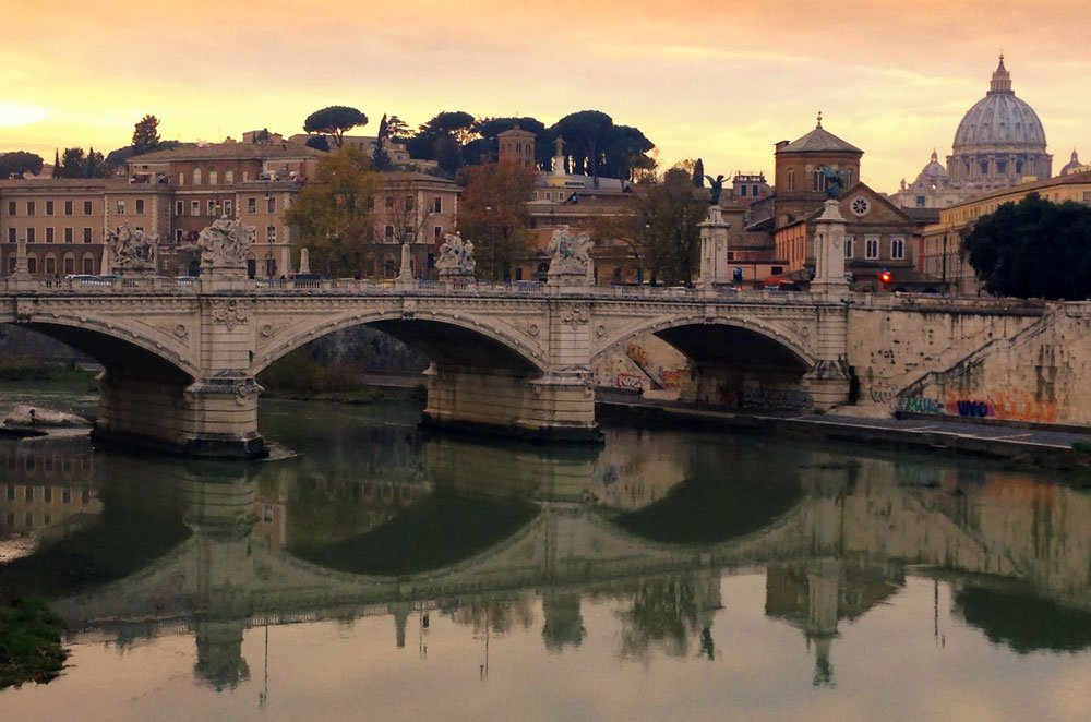 ornate bridge across river at dusk in rone which is the setting for many great italy movies
