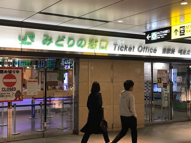 2 people walking past a jr-ticket-office