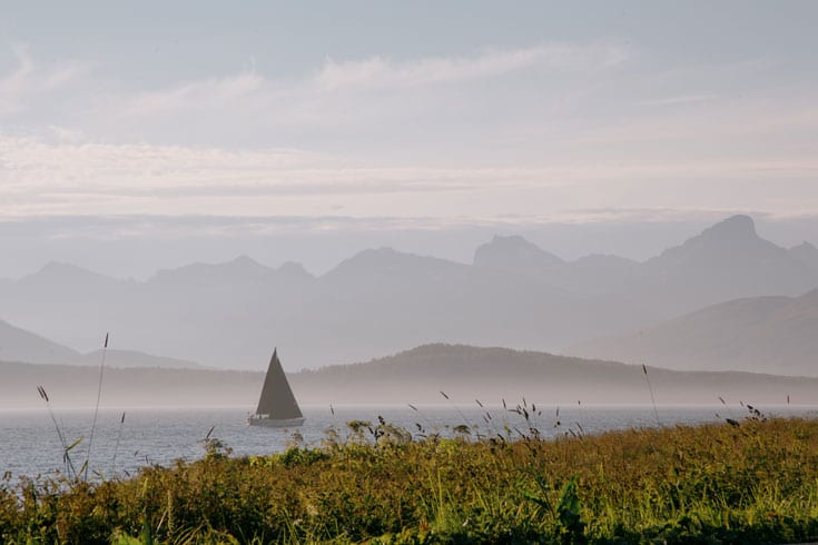 sailing boat on still lake with receding mountains in norway