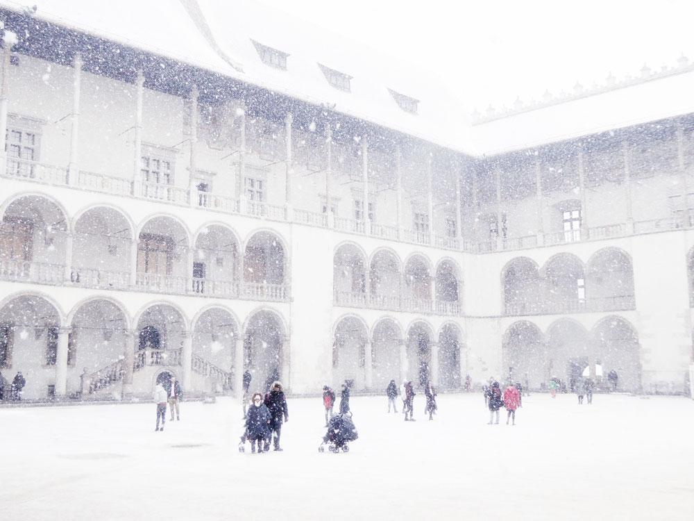 people walking in snow in castle courtyard in krakow poland