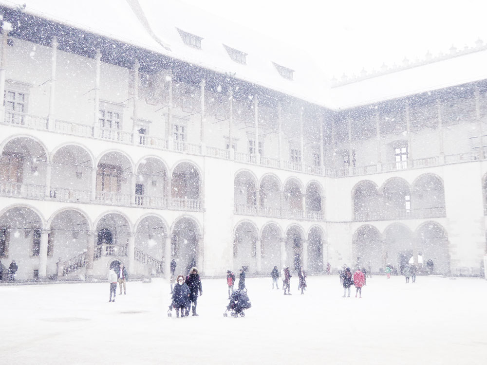 people walking in snow in castle courtyard in christmas in krakow poland