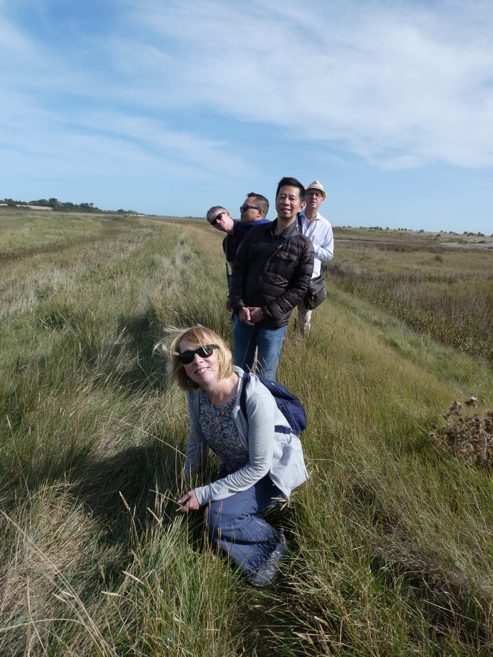 group of people posing on a pth surrounded by marshland and reed beds