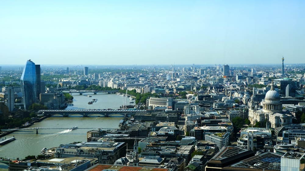 river thames with bridges and boats and london eye in distance