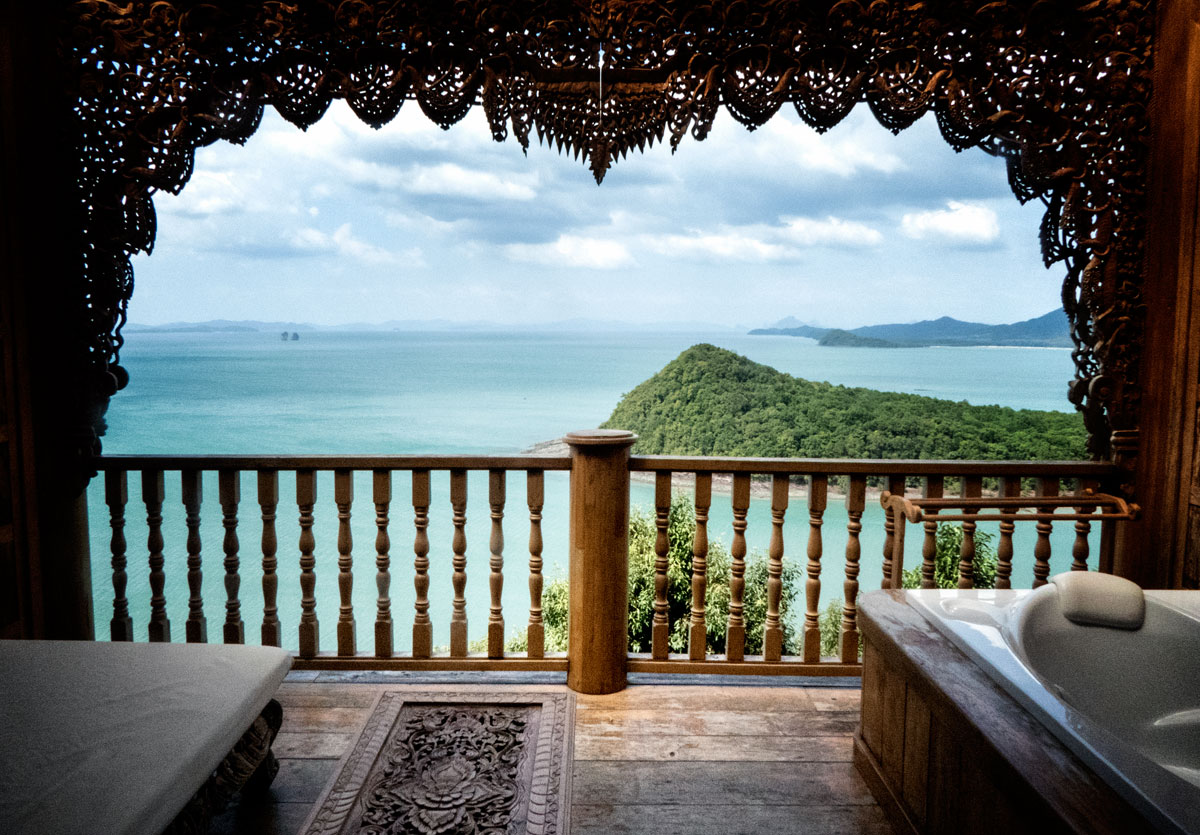 carved wooden hotel balcony looking over sea and island