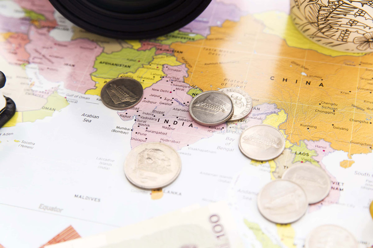 COINS ON A MAP OF THE WORLD AS A METAPHOR FOR AFFORDABLE LUXURY TRAVEL