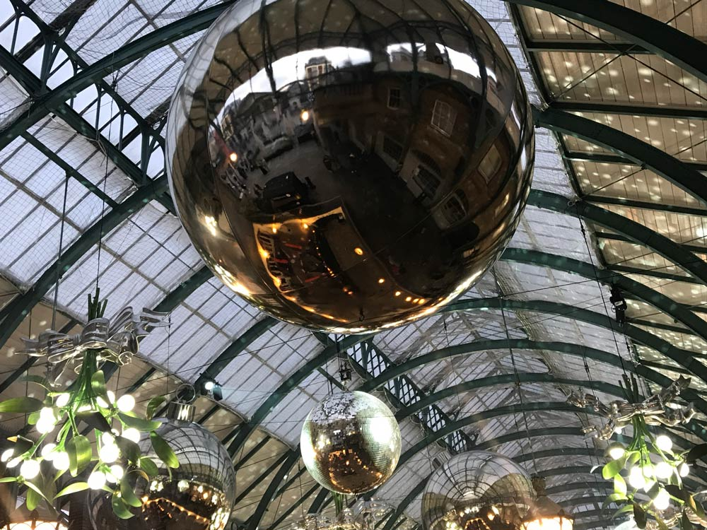 giant bauble hanging from iron and glass roog reflecting buildings of covent garden