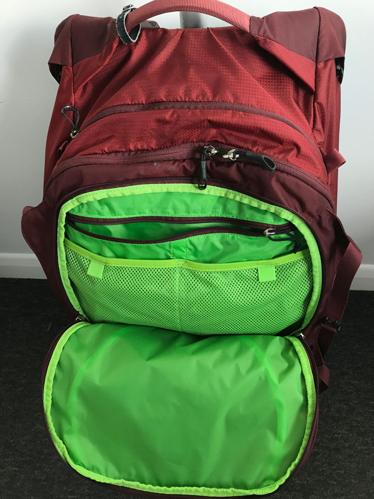 opened green and red front pocket of the Osprey Ozone 75 wheeled backpack