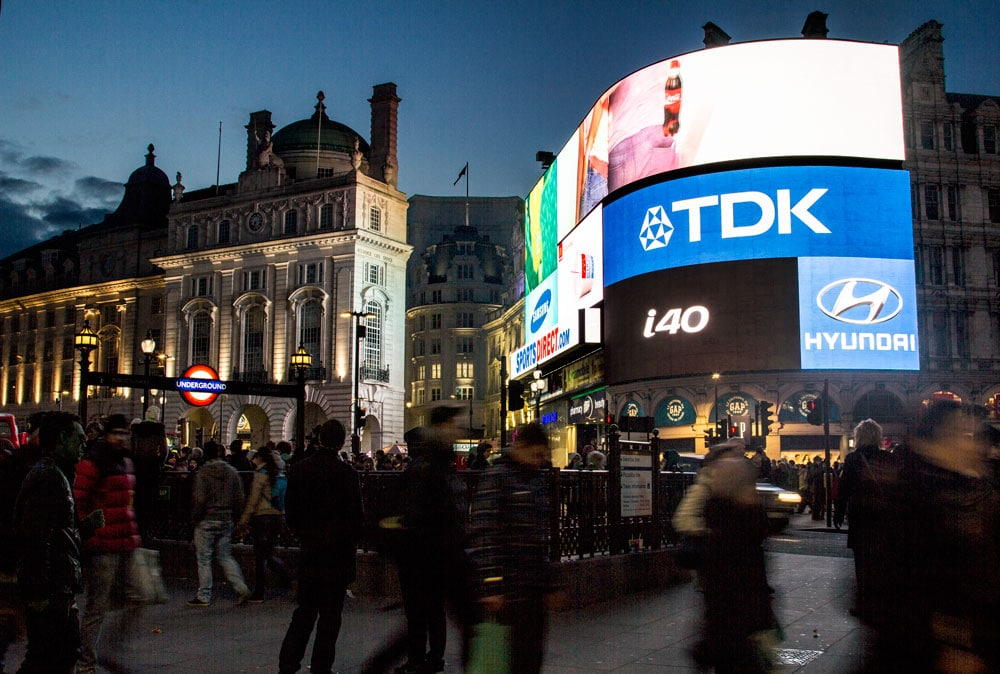 piccadilly circus at night with neon billboard and entrance to tube station
