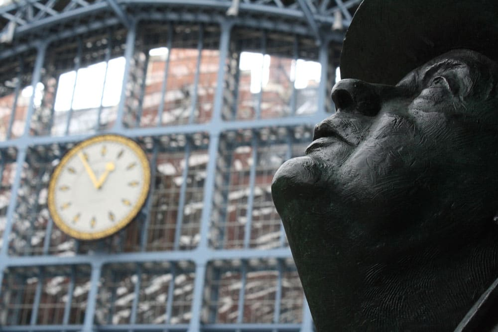 head of sir john betjeman statue in front of clock at st pancras station