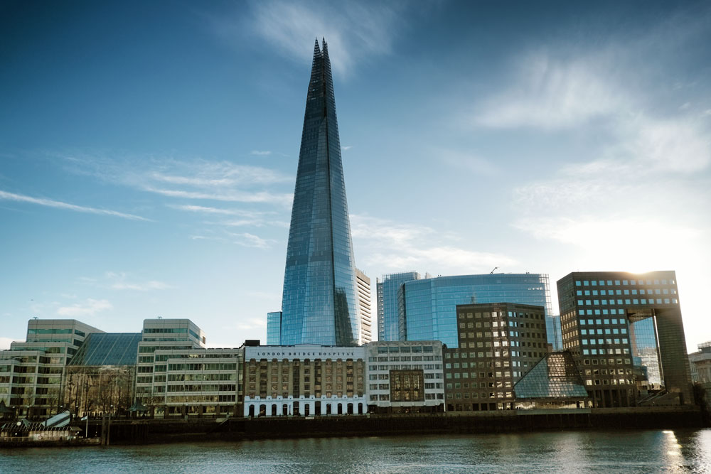 view of the shard from the borth bank of river thames under a blue sky