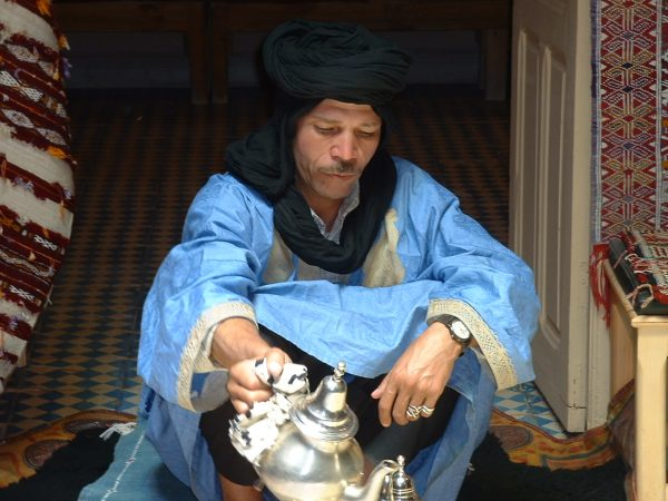 man in blue berber robes pouring tea