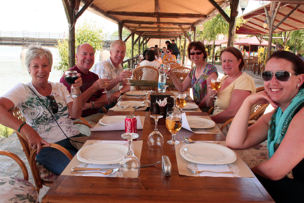 people sitting around dining table on group travel for singles tour