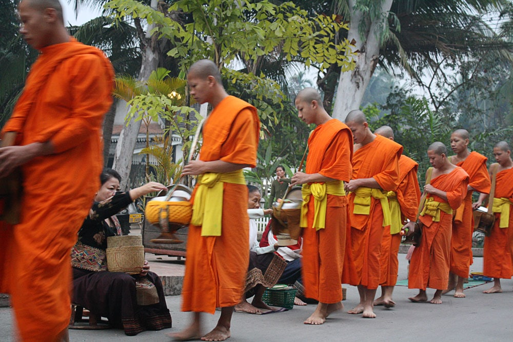 row of monks in saffron robes collection alms