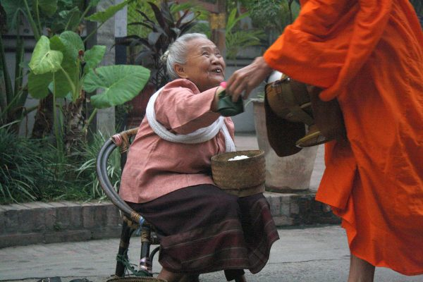 old woman giving alms to monk in saffron robe as an example of authentic travel