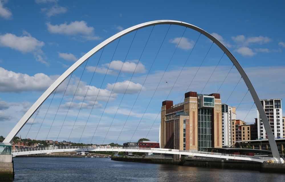 curved arch of newcastles milennium bridge and buildings along the riverfront