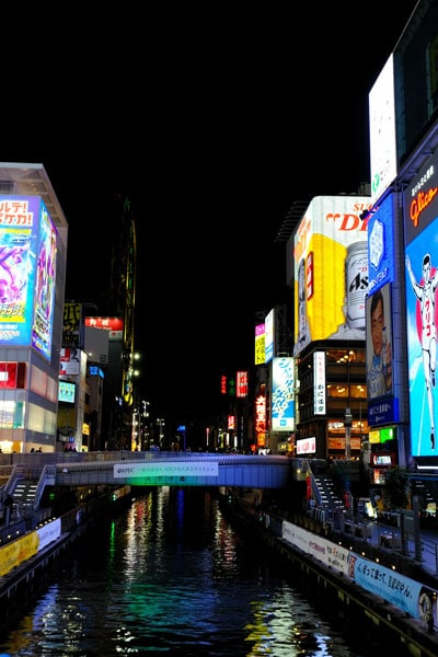 river in osaka at night lined with neon lit buildings