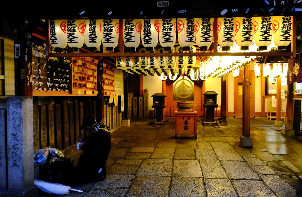man sitting on the ground in temple in osaka lit with chinese lantern