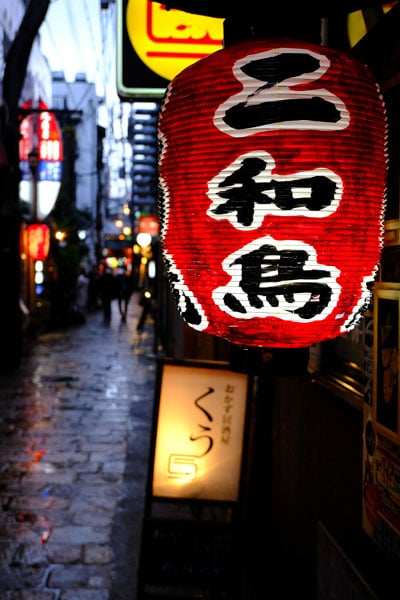 red and black chinese lantern in cobblestone street at night