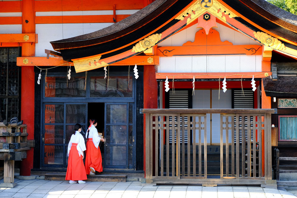 2 women dressed in white and saffron outfit entering building at yasaka shrine in kyoto