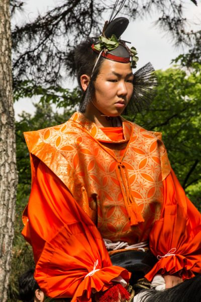 man in bright orange japanese costume on horse in kyoto
