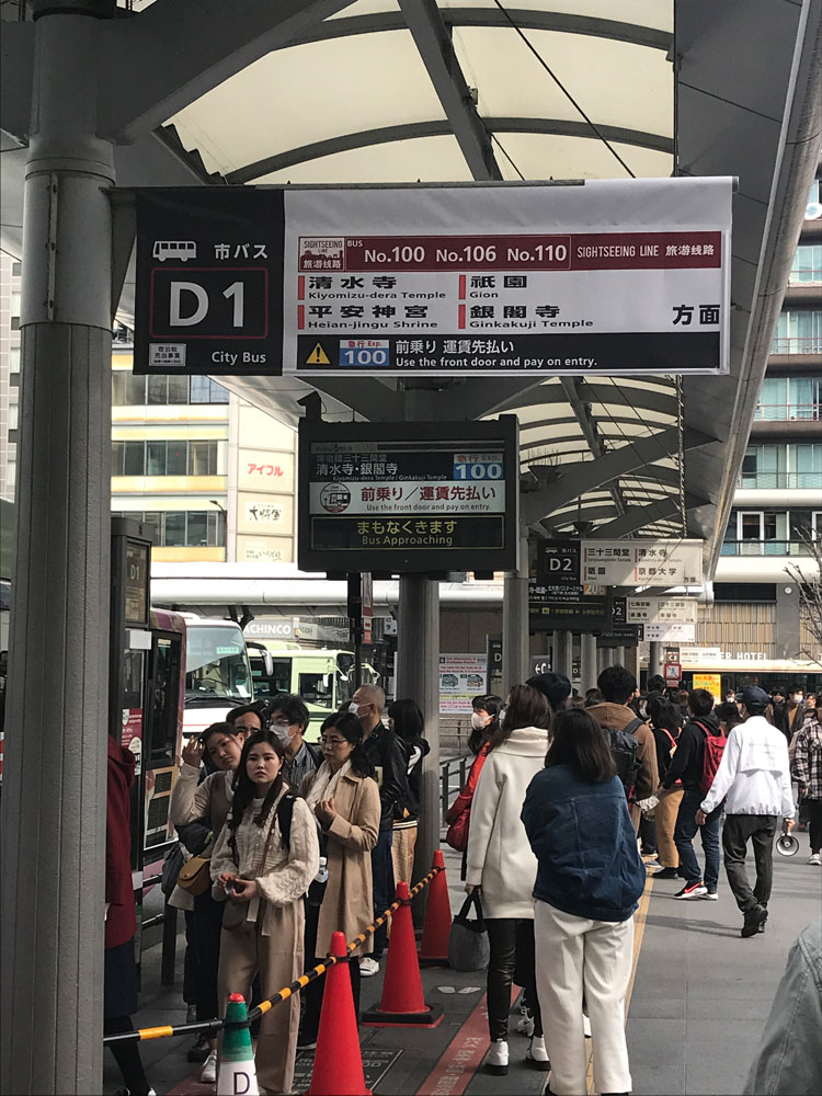 people queuing at bus stop in kyoto japan