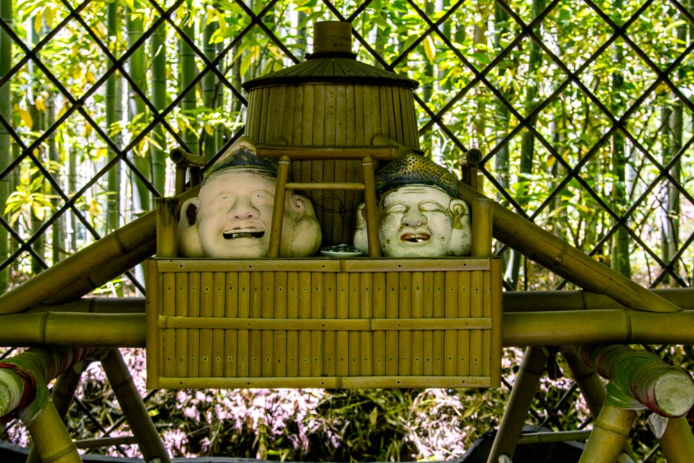 two statue heads with bamboo trees in background at nonomiya shrine kyoto