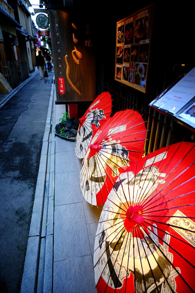 illuninated red japanese parasols on ground on pavement of narrow alley in kyoto