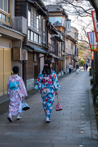 two women in kimonos walking along street with japanese traditional buildings