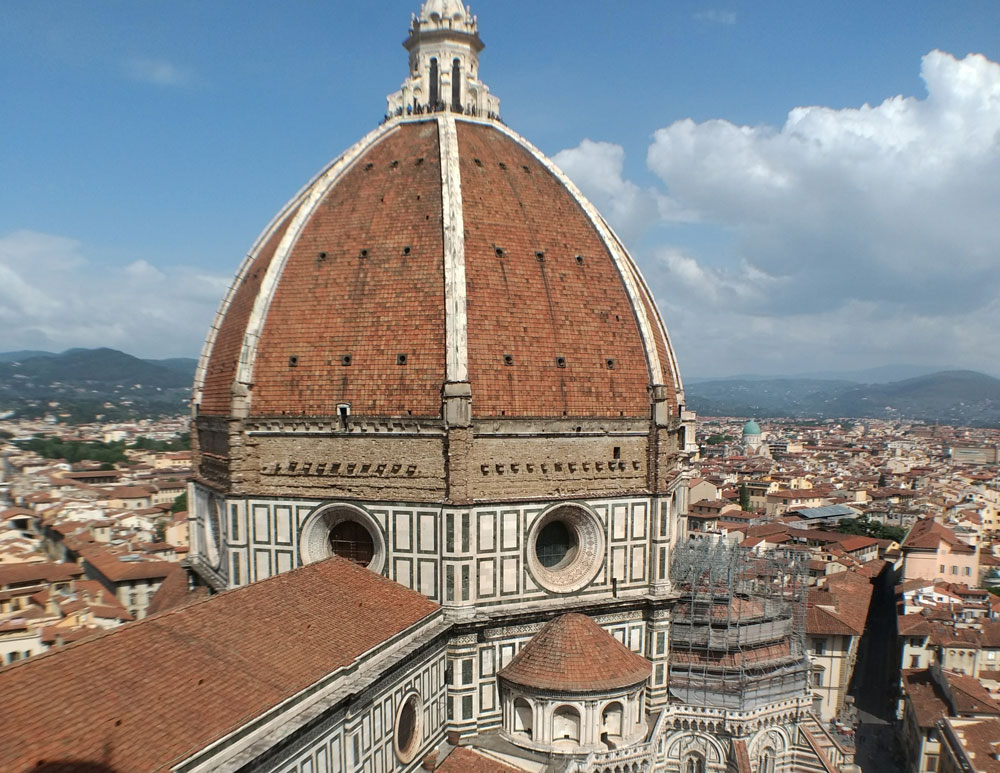 main dome of the duomo in florence surrounded by red tiled rooftops