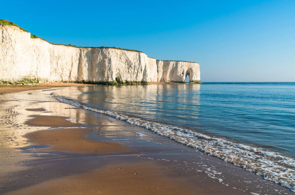 sandy-beach-against-a-cliff-face-with-limestone-arch-in-kent