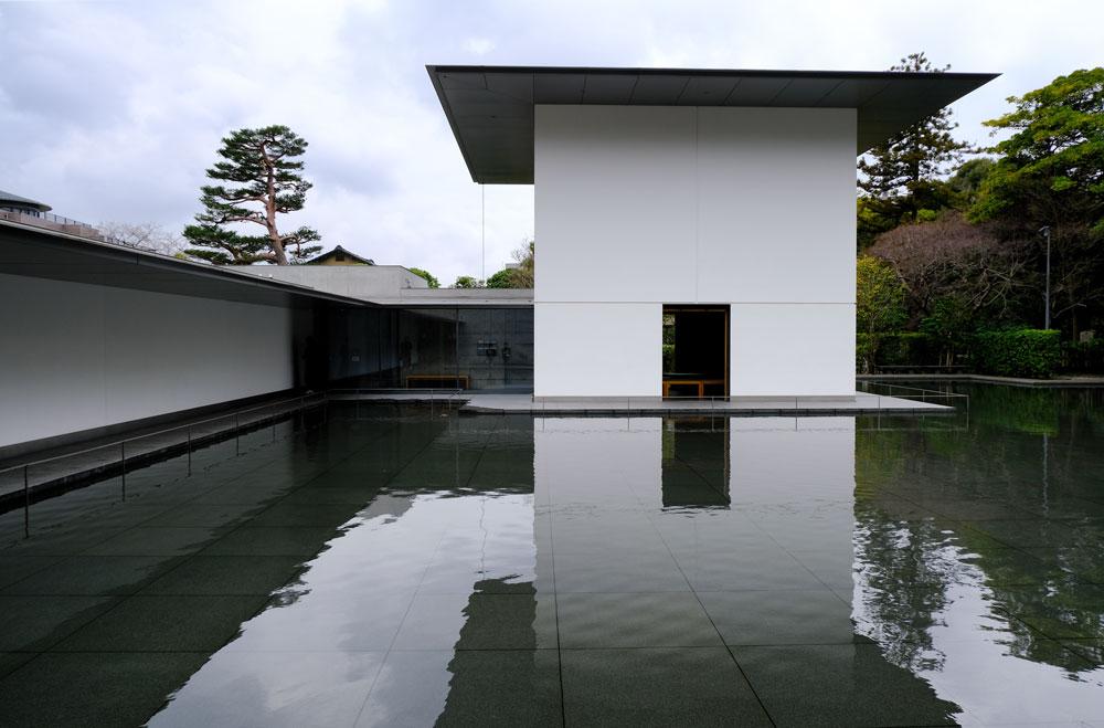 white geometric buildings around still pond in kanazawa-dr-sitzuki-museum