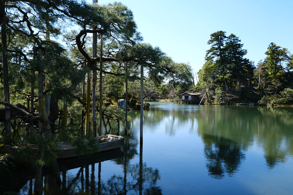 lake with reflections of tea house and trees at kenroku-en-garden