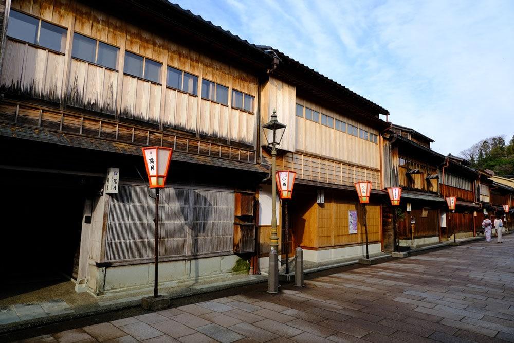 two women in kimonos walking past wooden fronted buildings in kanazawa japan